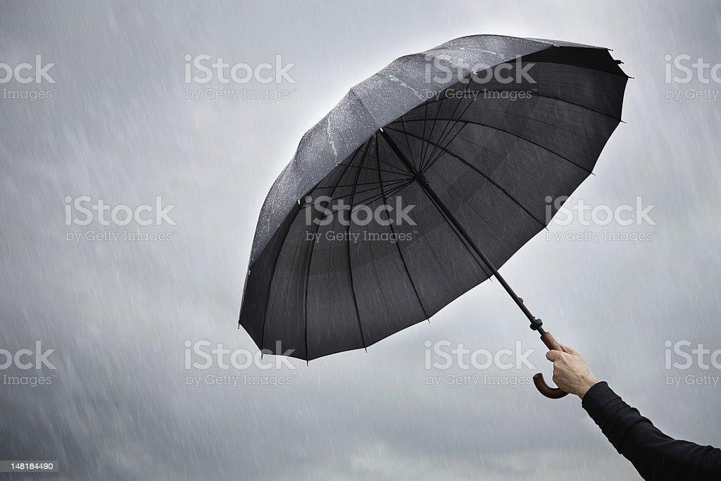 Person holding an open umbrella in the rain stock photo