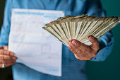 istock A Person Holding Bills and Money 1172759557