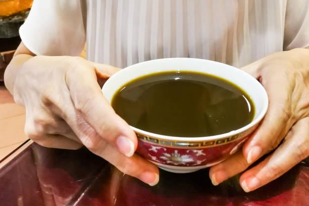 person, die therapeutische traditionelle chinesische medizin-suppe - schnelle suppen stock-fotos und bilder