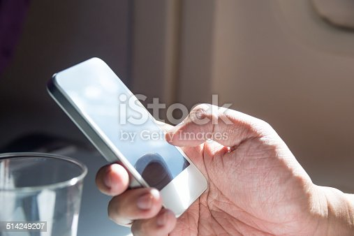 Close-up of person sitting in airplane using cell phone.