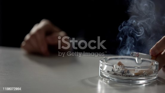 istock Person holding cigarette under ashtray full of butts, nicotine dependence 1158072954
