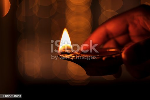 Happy Diwali - Man holding diya oil lamp with light bokeh background & copy space. Concept for Indian festive celebration, culture & tradition.