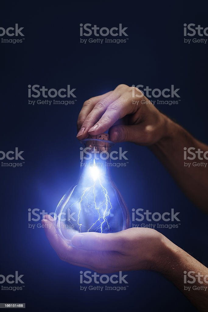 Person holding lightbulb with lightning superimposed inside royalty-free stock photo