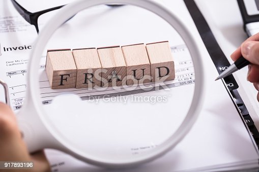 istock Person Holding Magnifying Glass And Examining Fraud Blocks 917893196