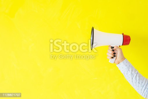 istock Person holding megaphone on empty yellow background 1128821707