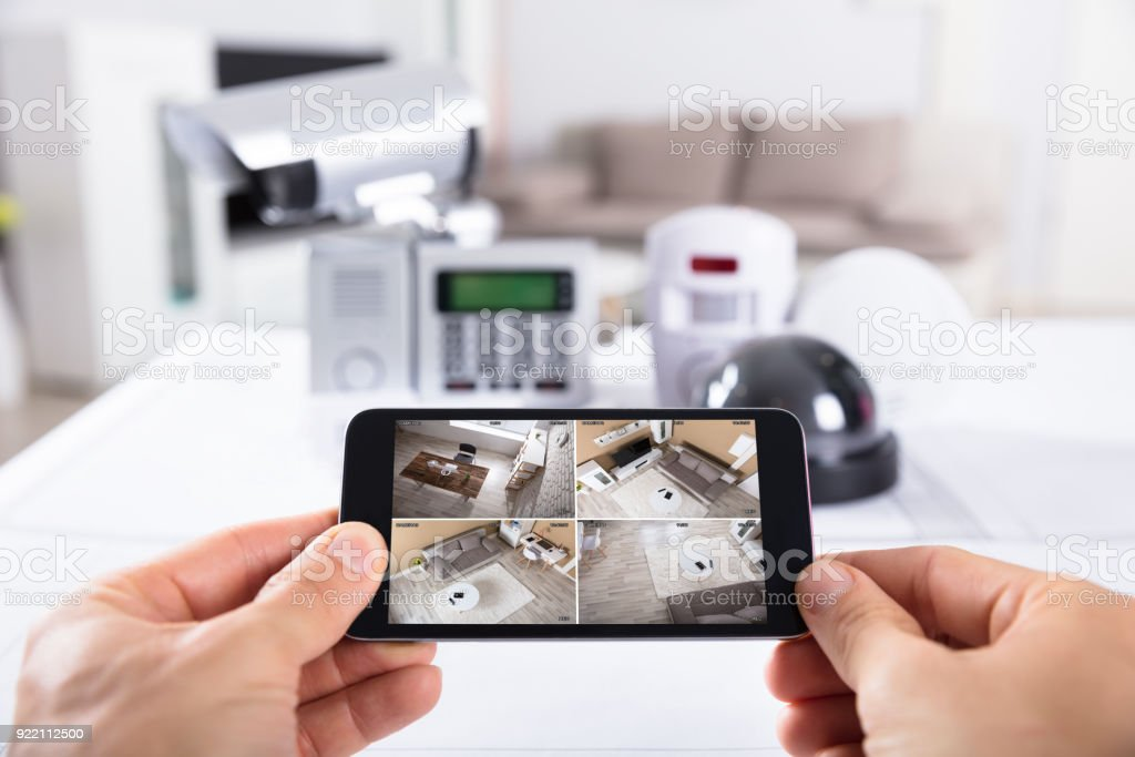 Person Holding Mobile Phone With Cctv Camera Footage On Screen Stock Photo  - Download Image Now