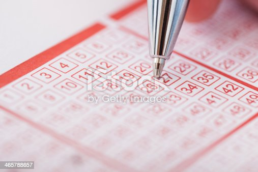 istock Person Holding Pen Over Lottery Ticket 465788657