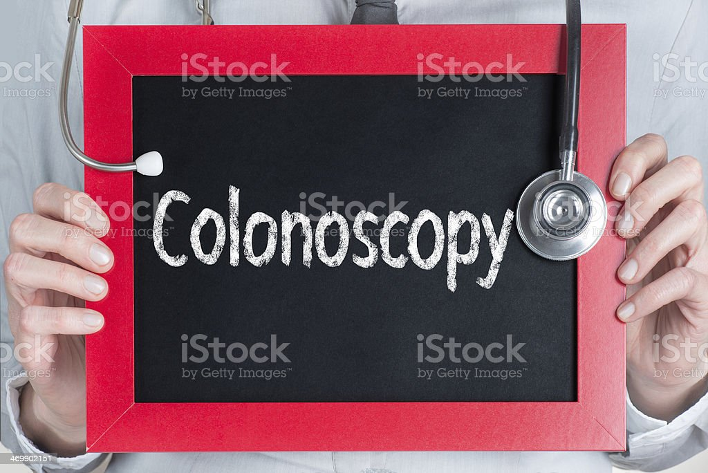 Person holding red chalkboard and that reads Colonoscopy  stock photo