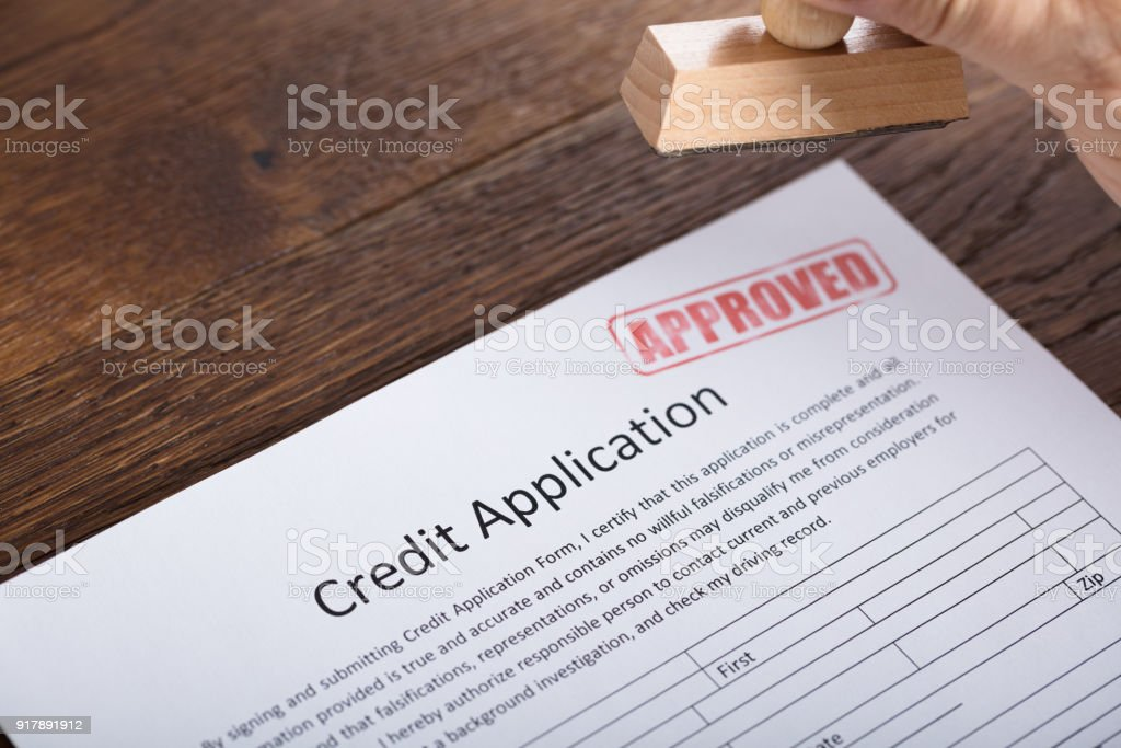 person holding stamp on credit application form stock photo more