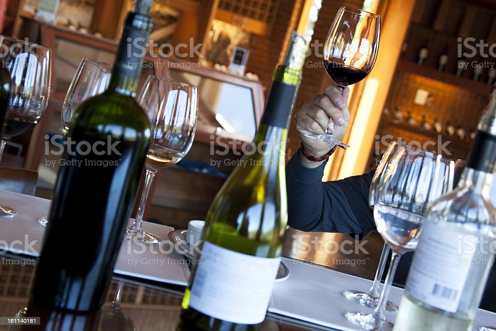 Person holding up glass at winetasting royalty-free stock photo