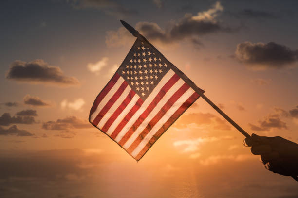 Person holding USA American flag on sunset background. stock photo