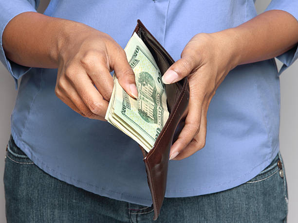 Person holding wallet with money stock photo