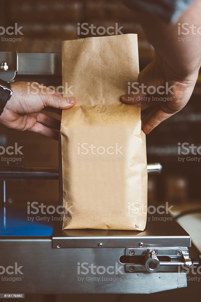 Person holding weighing coffee in bag stock photo