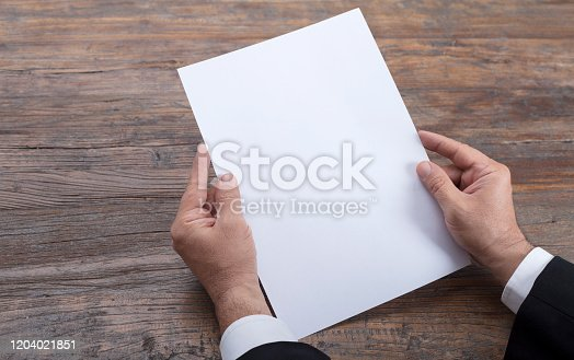istock Person holding white empty paper 1204021851