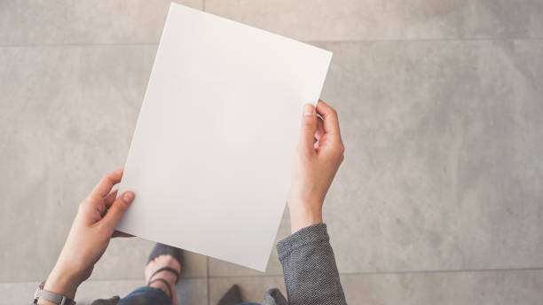 Person holding white empty paper stock photo
