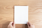 istock Person holding white empty paper 999682874
