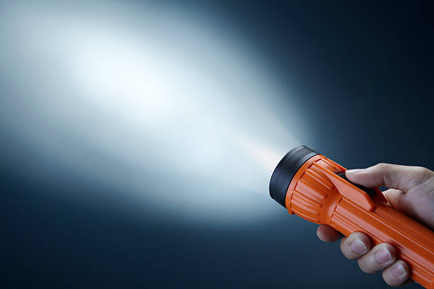 Person holdings orange flashlight searching in darkness stock photo