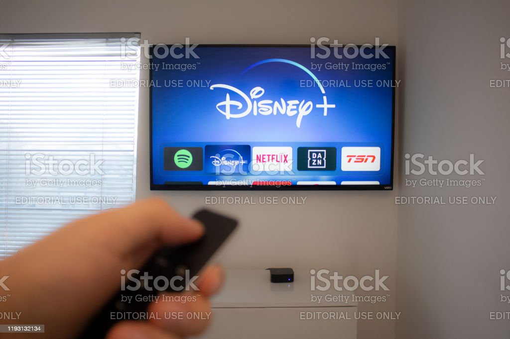 Person holds an Apple TV remote using the new Disney+ app on a Vizio TV. Disney+ video streaming service will exclusively show Star Wars: Jedi Template Challenge. Calgary, Alberta. Canada Dec 5 2019: Person holds an Apple TV remote using the new Disney+ app on a Vizio TV. Disney+ video streaming service will exclusively show Star Wars: Jedi Template Challenge. Adult Stock Photo