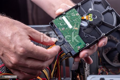 person holds dusty hdd from desktop for cleaning or upgrade old broken hardware. hard drive sata and power connection interface close up.upgrade desktop hardware.