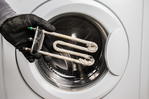 Person holds in his hand a damaged electric heating element from the washing machine. Repair and restoration work