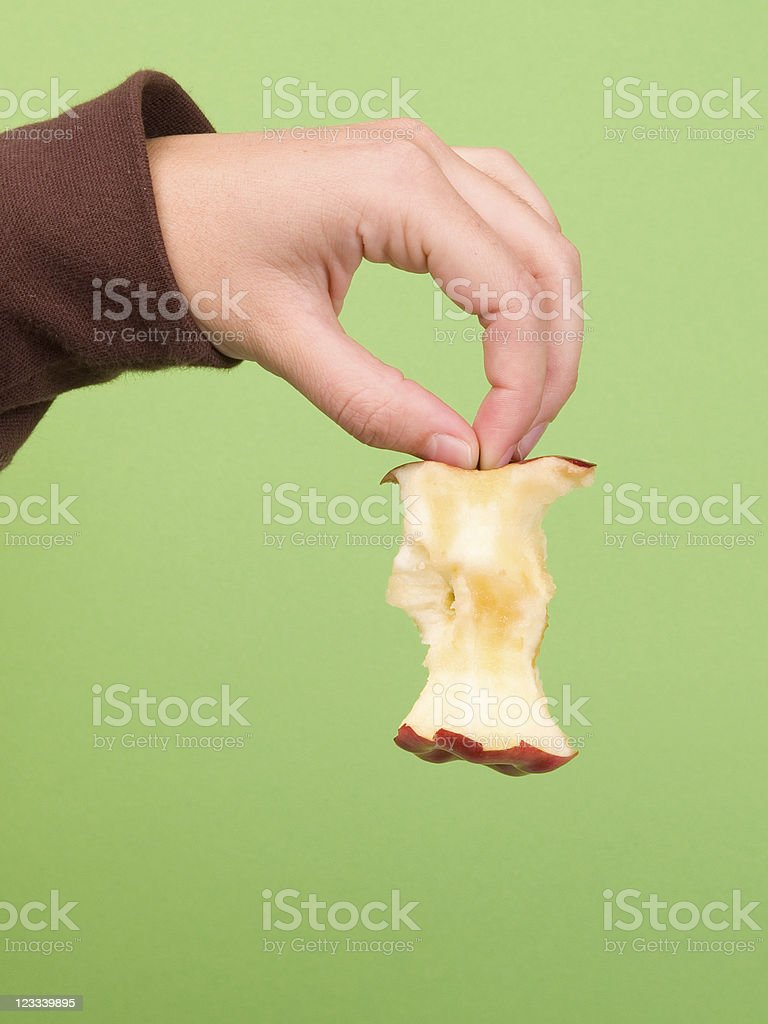 A person holds up an apple core against a green background royalty-free stock photo