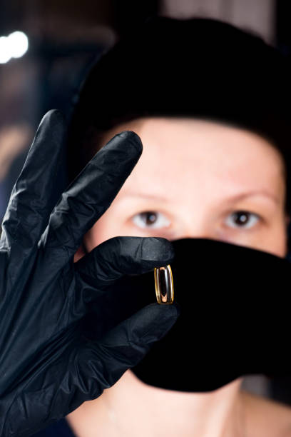 person in a black medical mask and gloves holds a pill capsule in fingers stock photo