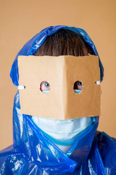 person in a home-made protective suit and medical mask in anxiety from a coronovirus pandemic stock photo