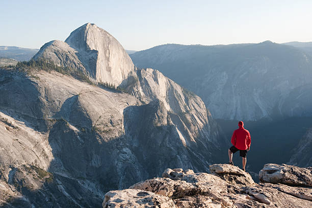 Person in a red coat standing looking at a mountain stock photo