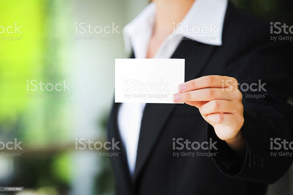 A person in a suit holding up a blank business card stock photo