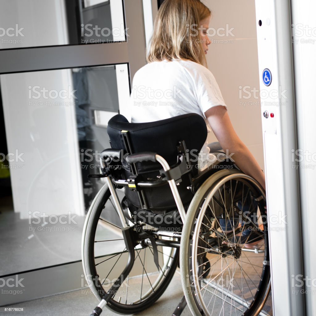 Person in a wheelchair entering an elevator stock photo