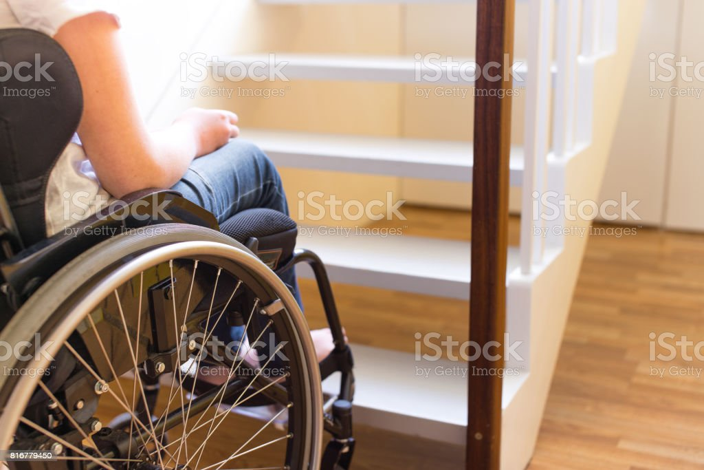 Person in a wheelchair in front of a stair stock photo