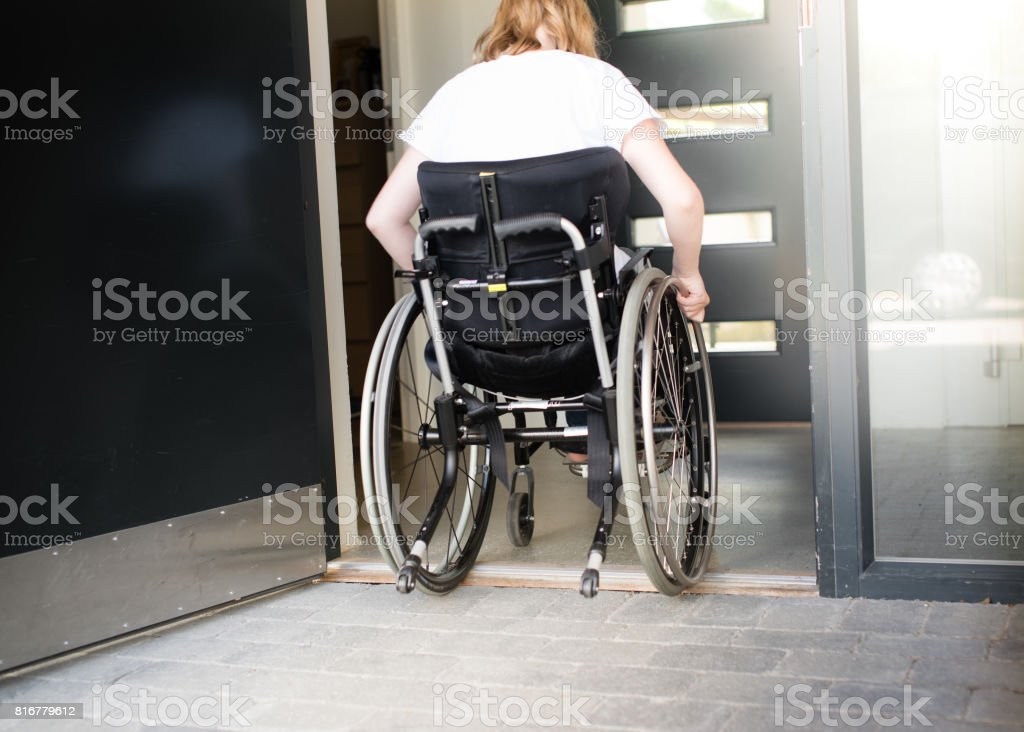 Person in a wheelchair moving over a low doorstep stock photo