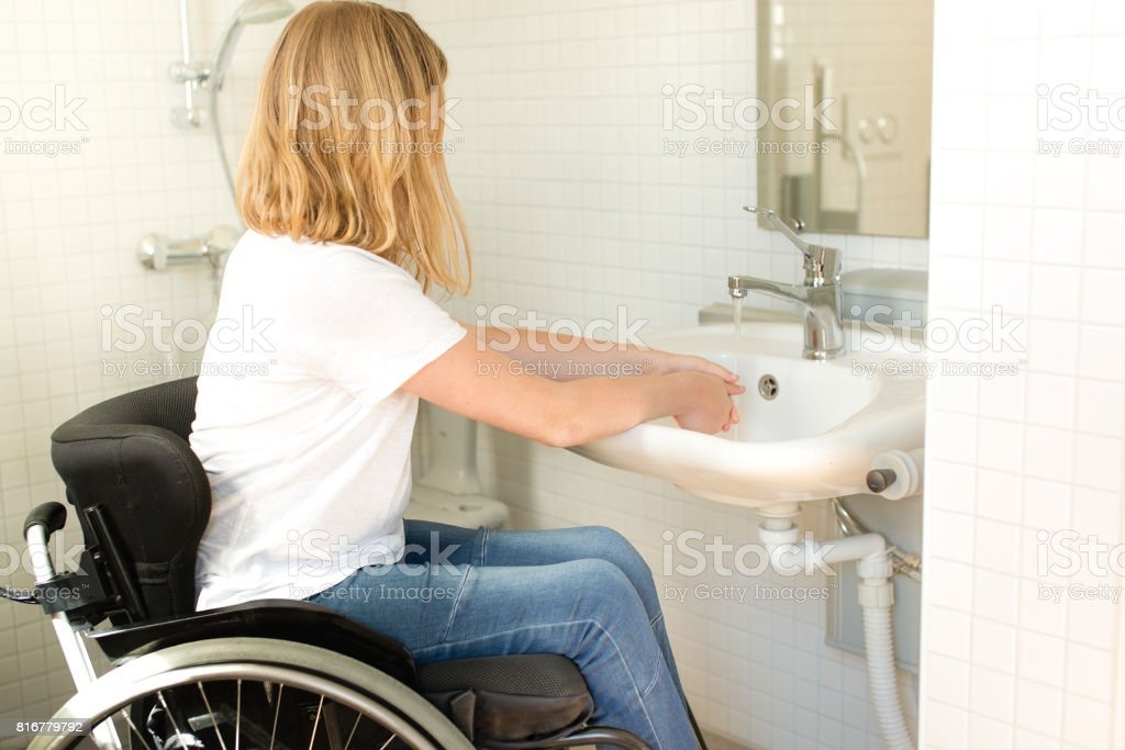 Person in a wheelchair washing hands stock photo