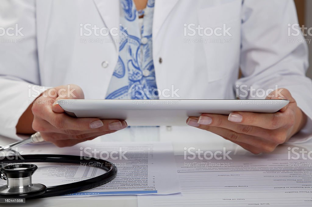 A person in a white coat using a tablet stock photo