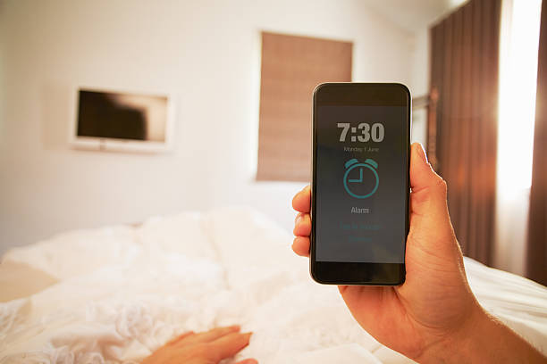 person in bed turning off phone alarm - alarm clock bildbanksfoton och bilder
