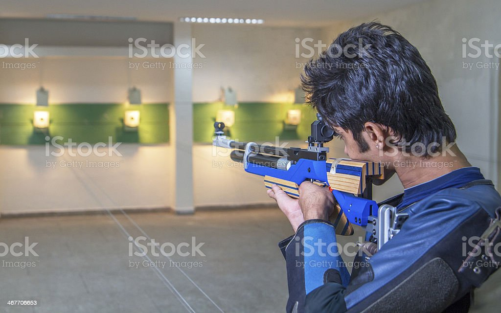 Person in blue aiming at a target during practice stock photo
