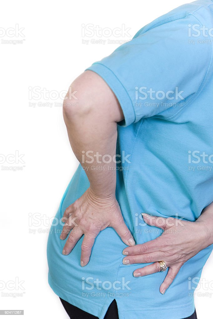 A person in blue shirt clutching their hip in pain stock photo