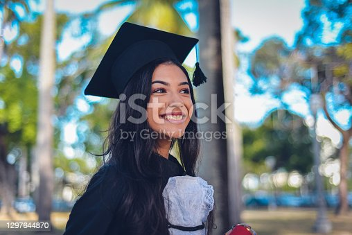 A young woman wearing a cap and gown, mixed race Hispanic and Caucasian. She is a university or high school graduate, smiling at the camera.