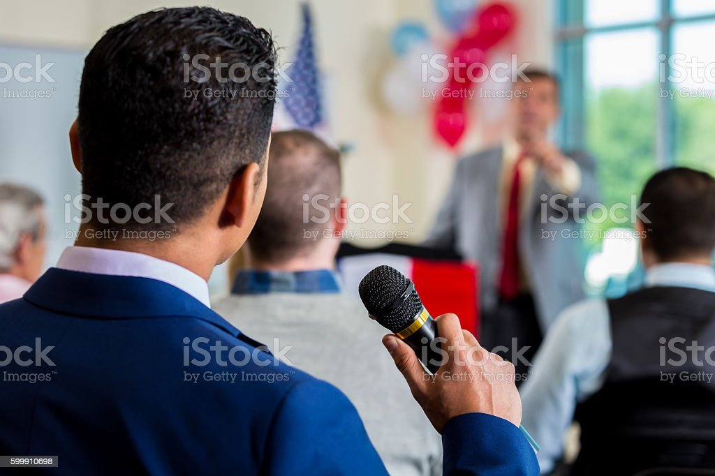 Person in crowd asking question during town hall meeting stock photo