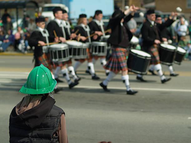 person in green hat watching drummers walk by in the parade - geçit töreni stok fotoğraflar ve resimler