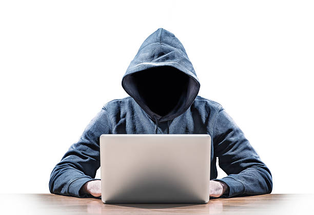 person in hooded sweater using a laptop on wooden table - hacker stock photos and pictures