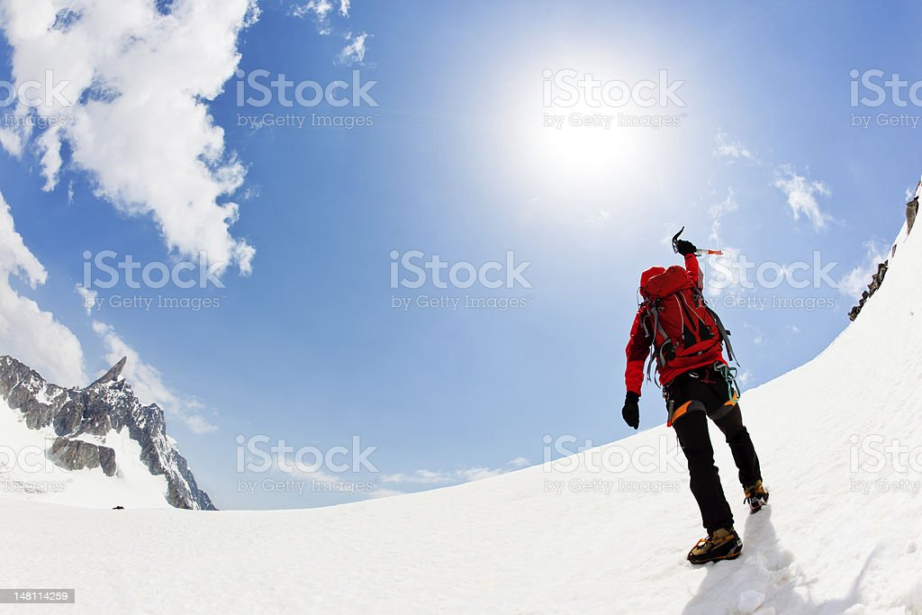 Person in mountain climbing gear standing near the summit royalty-free stock photo