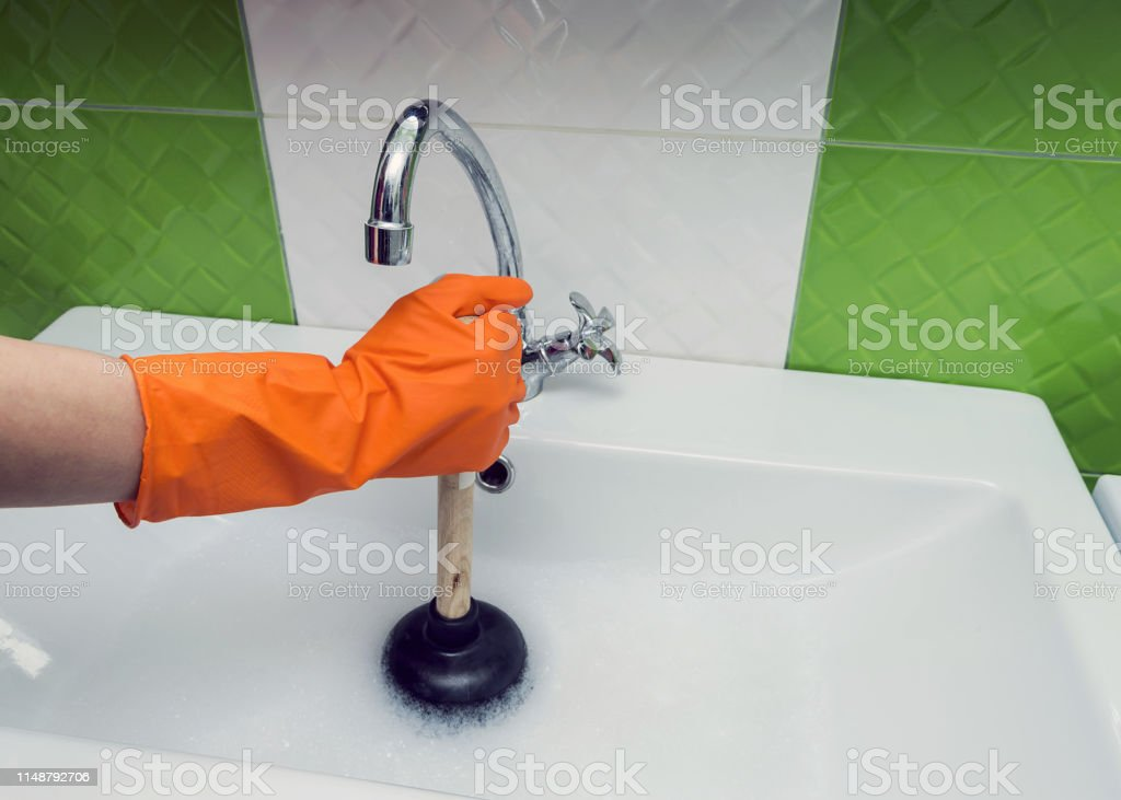 Person in protective orange gloves unblocking a clogged sink with...