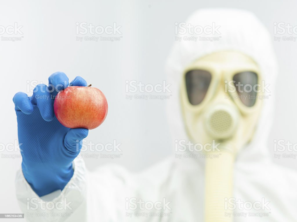 person in protective suit holding ripe apple royalty-free stock photo