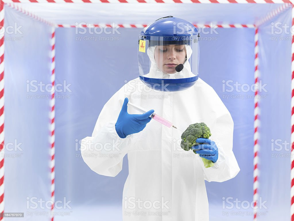 person in protective suit injecting a vegetable royalty-free stock photo