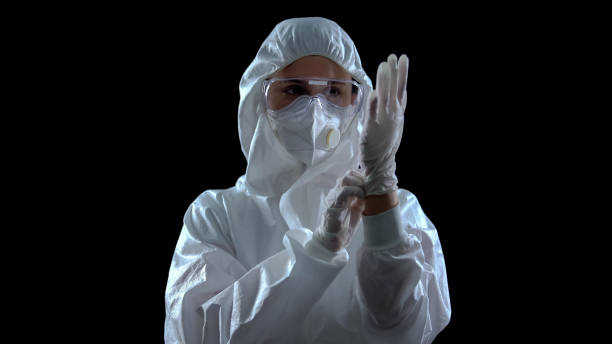 person in protective suit wearing rubber gloves against dark background, toxins - indumento protettivo foto e immagini stock