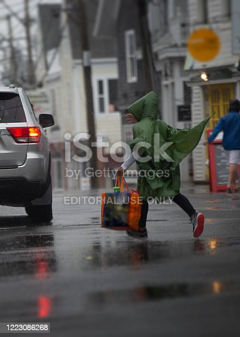 Provincetown, Massachusetts - 6/28/2018: A person runs across Commercial Street on a rainy summer day