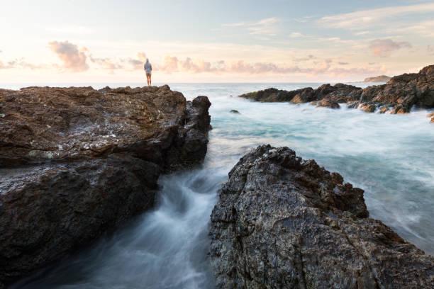 Person in Rocky Seascape stock photo