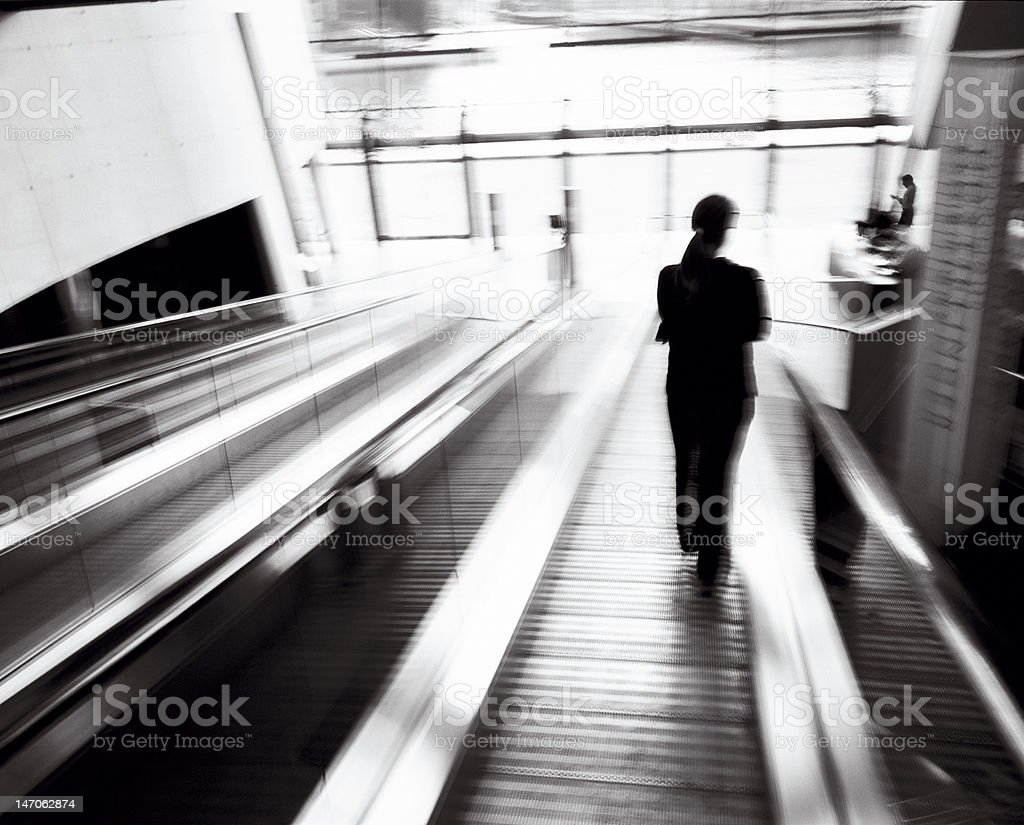 Person in silhouette on escalator royalty-free stock photo
