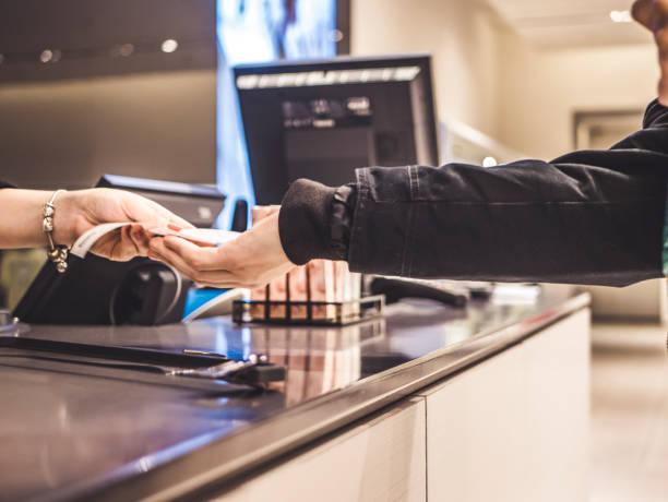 person im shop bezahlen mit bargeld und geldbeutel hautnah - kassenbon stock-fotos und bilder